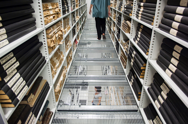 Employee in the Statens Avissamling between shelves