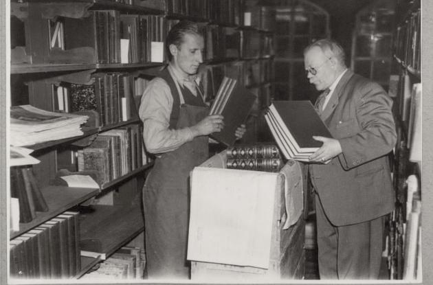 Library staff among books and bookshelves. Older
