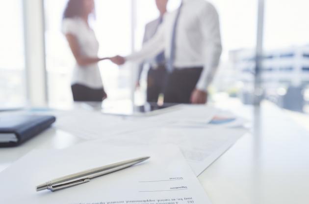 Faded handshake over desk