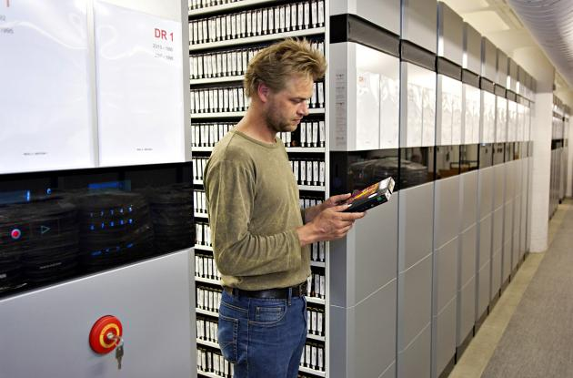 Employee among shelves with videotape