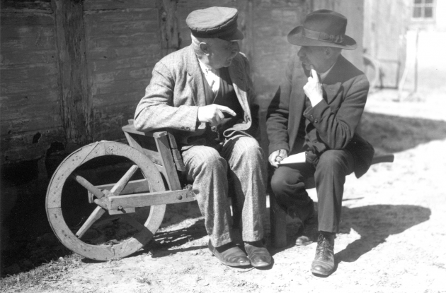 Older men in conversation sitting on old wheelbarrow