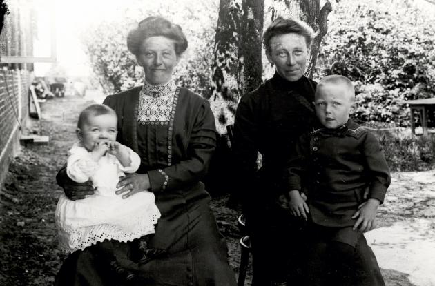 Two South Jutland women, each with their child on their lap