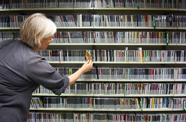 Employee at shelves with CDs