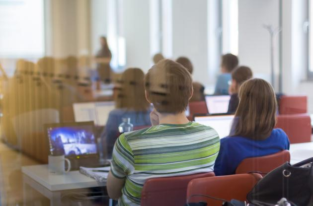 Students with laptops in meeting room