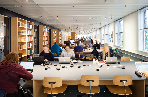 Students with laptops in library room