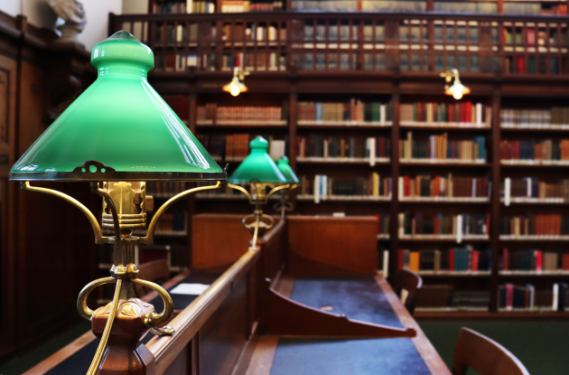 Reading room with classic green lamps and books on shelves