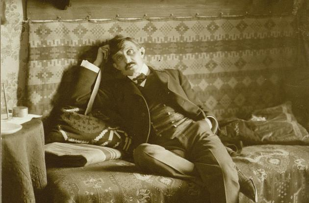 Author Herman Bang posing on bed