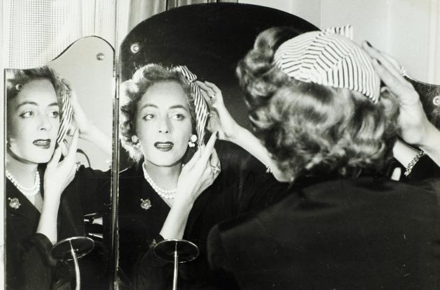 Christine Jorgensen straightens her hat in front of a dressing table with a mirror