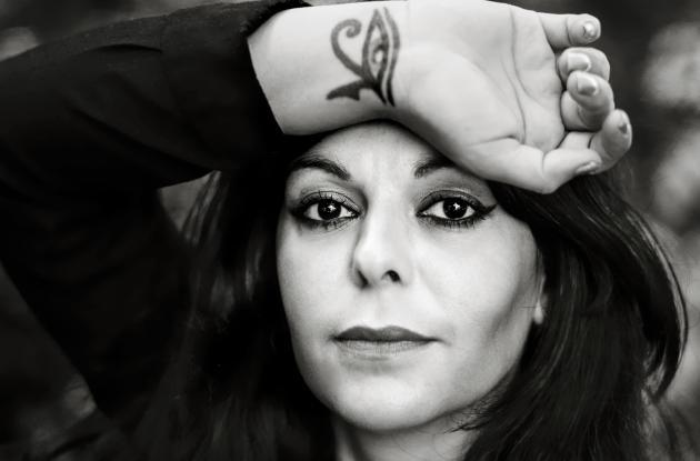 Sort-hvidt pressefoto af digteren Shadi Angelina Bazeghi, der holder sit håndled op på sin pande. På håndleddet er en tatovering af et øje.