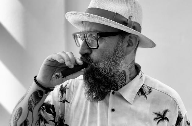 Sort-hvid billede af digteren Claus Høxbroe i sommerskjorte og hat, ryger en cigar.