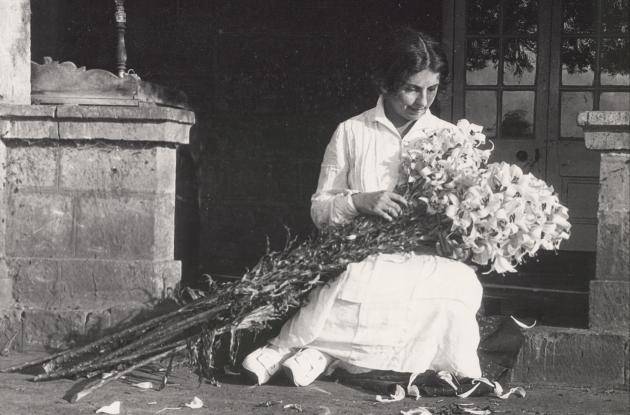 Karen Blixen is sitting on a step with a large bouquet of lilies