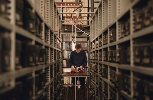 Anders Toftgaard flips through books in Det Kgl. Bibliotek's Danish Hall. Still from the movie A Word for Human