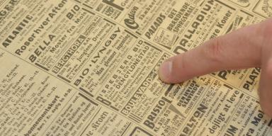 Finger points to text in newspaper