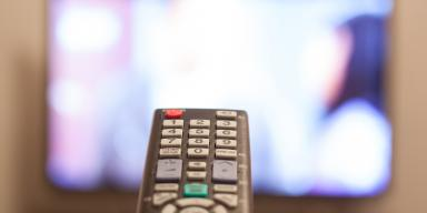 Remote control in front of TV screen