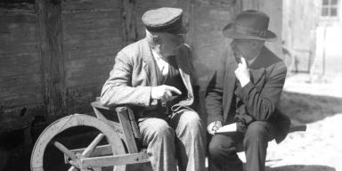 Older men in conversation sitting on old wheelbarrow