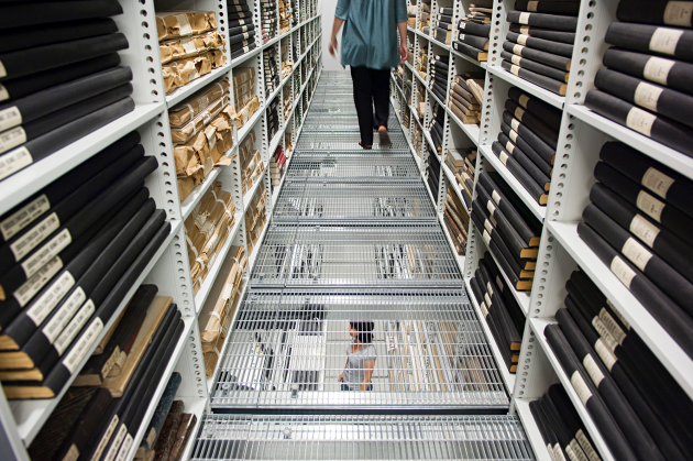 Employee in the Statens Avissamling between shelves