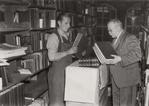 Biblioteksmedarbejdere blandt bøger og reoler. Ældre