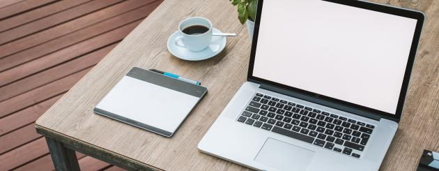 Table with laptop, coffee and writing utensils