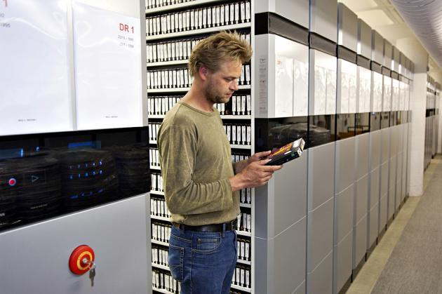 Employee among shelves with videotape