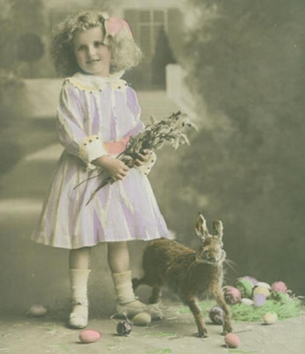 Pige med blomsterbuket står ved siden af en hare