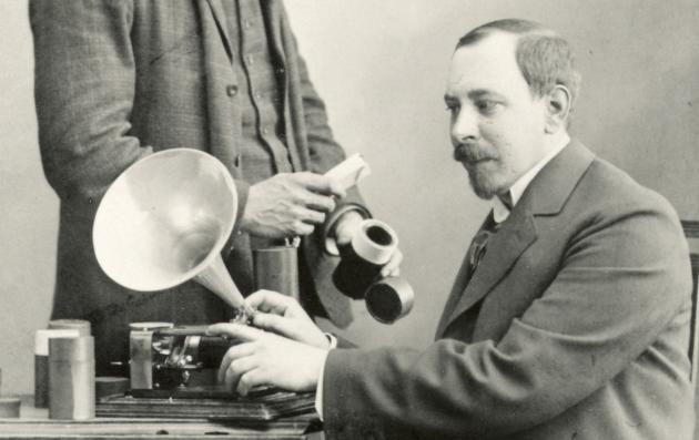 En stående mand holder en valseæske mens en siddende mand betjener en fonograf
